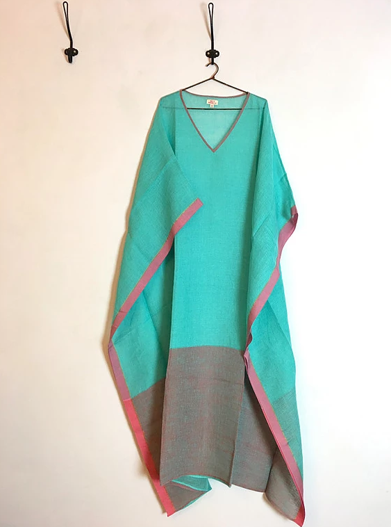 A green hand-loom cotton kaftan hanging on a hanger